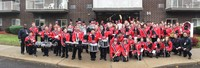 A picture of the Marching Band posing for a photo outside of the school